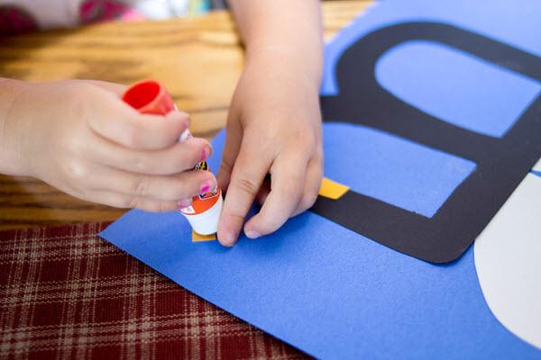 child adding stripes to bee craft