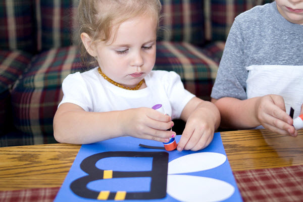 little girl gluing pieces on bee craft