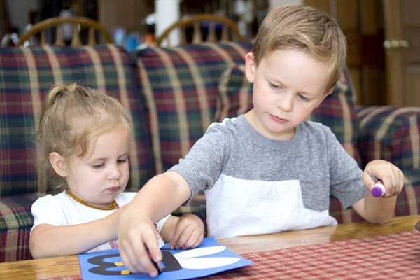 two children gluing pieces on a craft