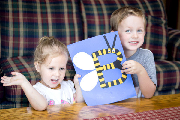 two children with their finished bee craft