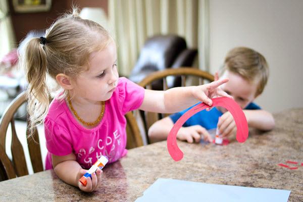 child gluing letter C craft