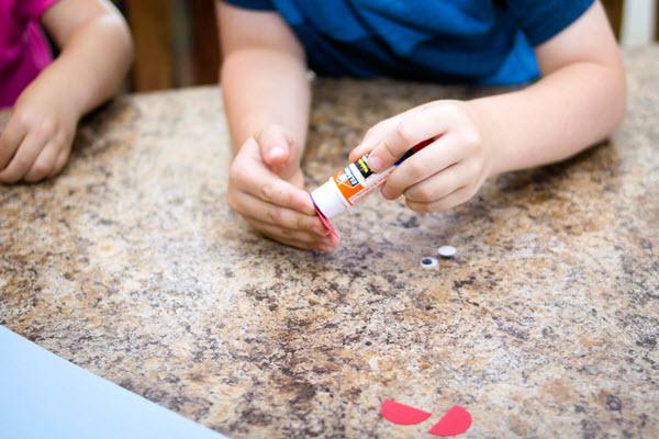 child applying glue to letter c craft