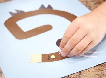 child adding a googly eye to her letter G craft
