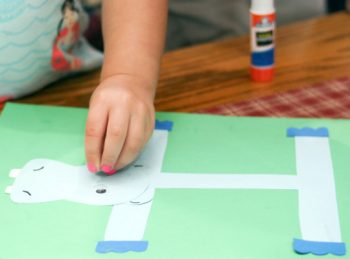 child adding a googly eye to her letter H craft