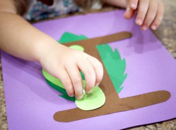 child gluing an inchworm on the letter I craft