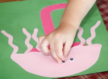 child gluing an eye to her letter j craft