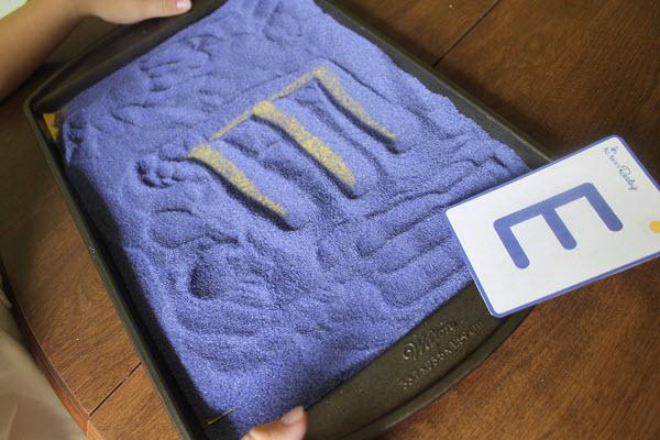 the letter E written in a salt tray