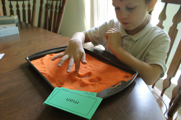 child practicing sight words with a salt tray