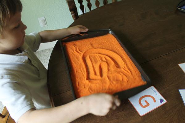 child shaking salt tray to erase
