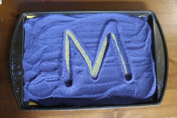 letter M and a colored background in a salt tray