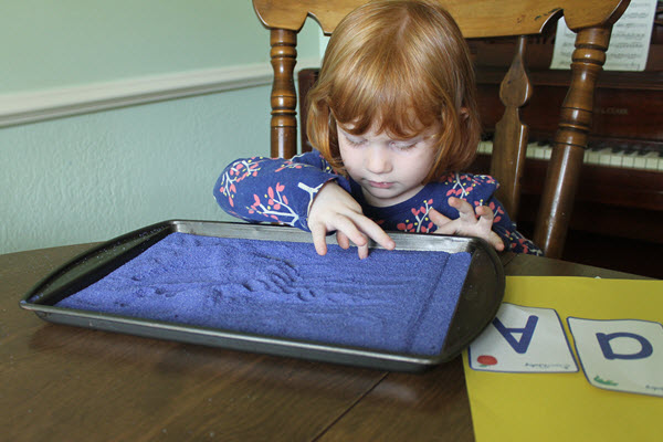 Young child writing in a salt tray