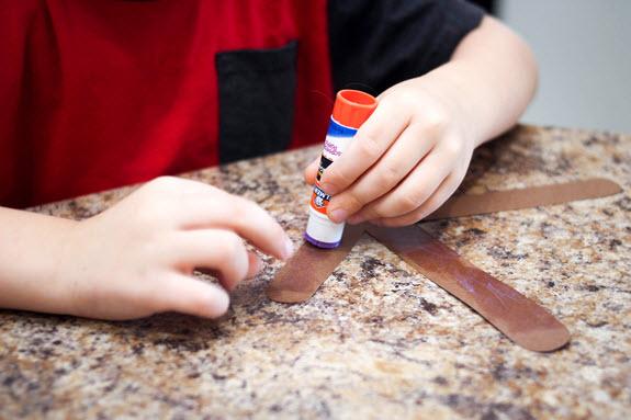 child applying glue to letter k craft