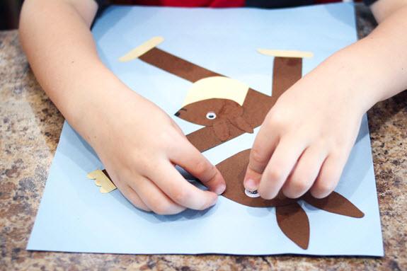 child applying googly eyes to the letter k craft