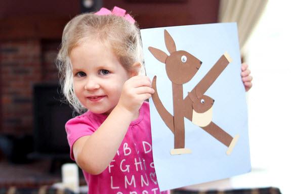 little girl holding up her letter k craft