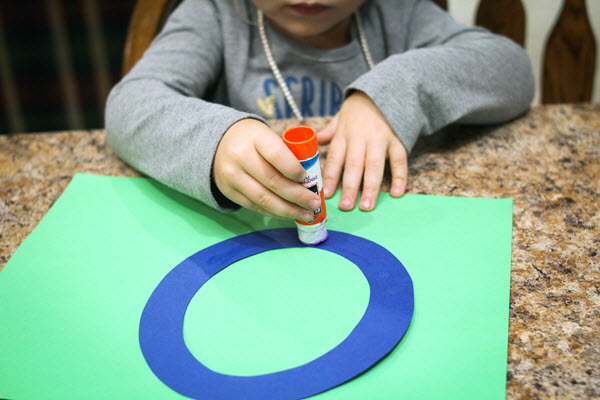 child putting glue on her letter o craft