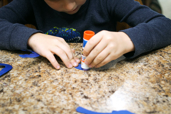 boy gluing tentacles for his letter o craft