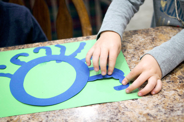 child gluing tentacles to her letter o craft