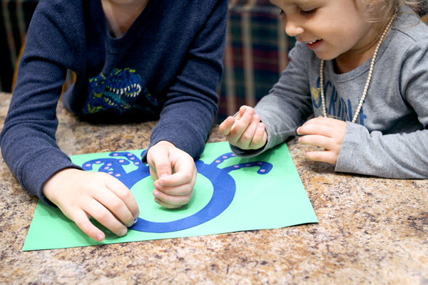 children attaching tiny dots to their letter o craft