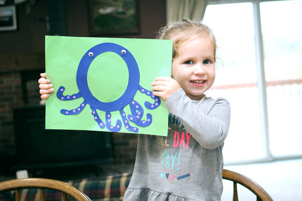 little girl showing off her completed letter o craft