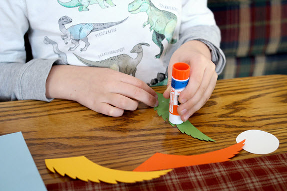 boy applying glue to tail feathers for his letter p craft
