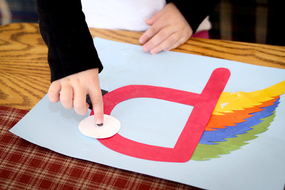 child gluing a googly eye onto his letter p craft