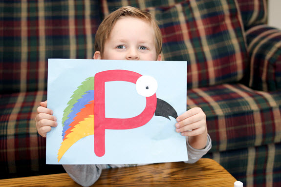boy holding up his finished letter P craft