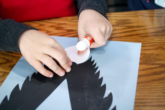boy gluing head on letter v craft