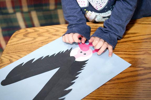 child gluing beak on letter v craft