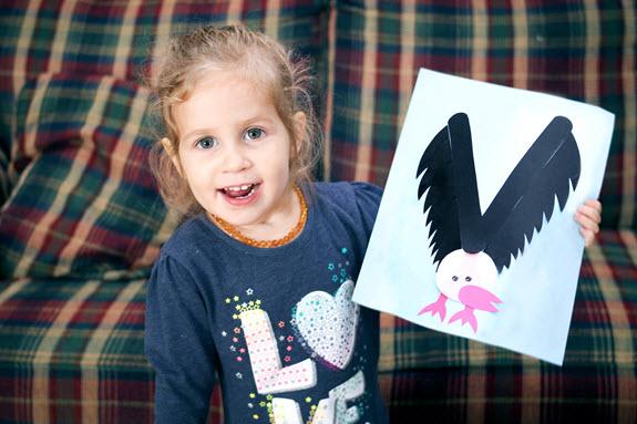 little girl showing finished letter v craft
