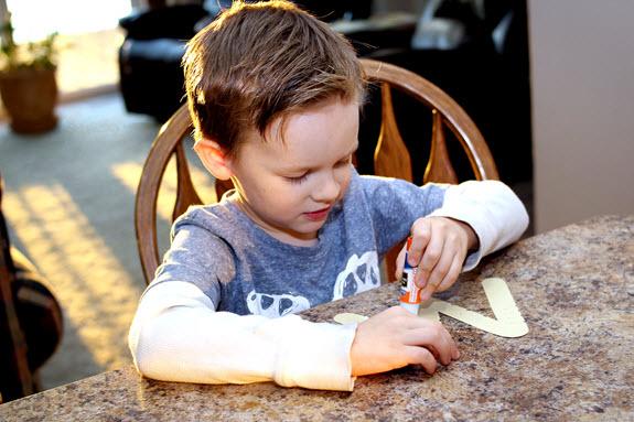 boy gluing letter w craft