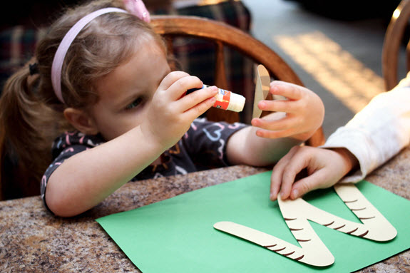girl gluing letter w craft