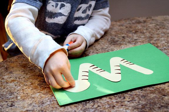 boy gluing head on letter w craft