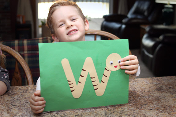 boy shows finished letter w craft
