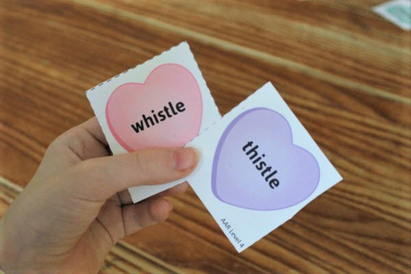 child holding rhyming activity cards