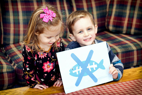 children show off their finished letter x craft