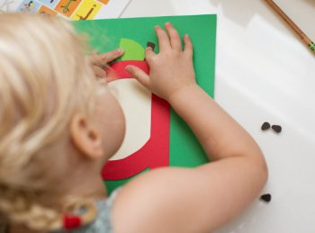 little girl finishing her lowercase letter a craft