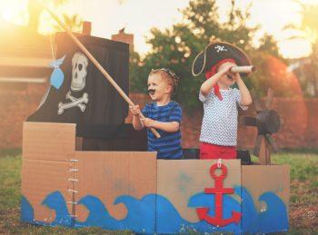 kids playing in a cardboard pirate ship