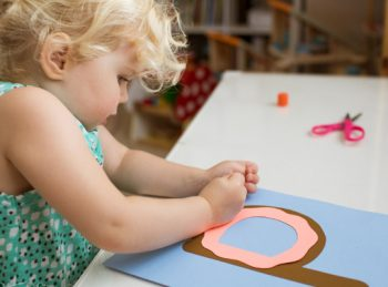 little girl drawing sprinkles on her lowercase d craft