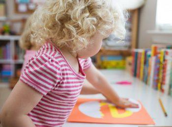 little girl creating lowercase e craft
