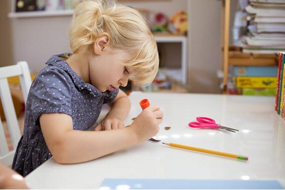child glues her lowercase h craft