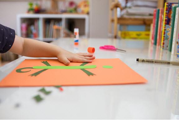 Child assembles letter I craft