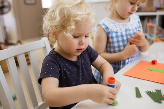 child glues letter i craft