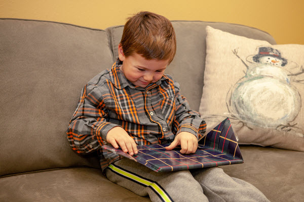 little boy unwraps picture book for book advent calendar