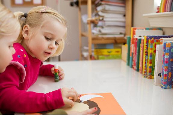 girl assembles her uppercase letter O craft