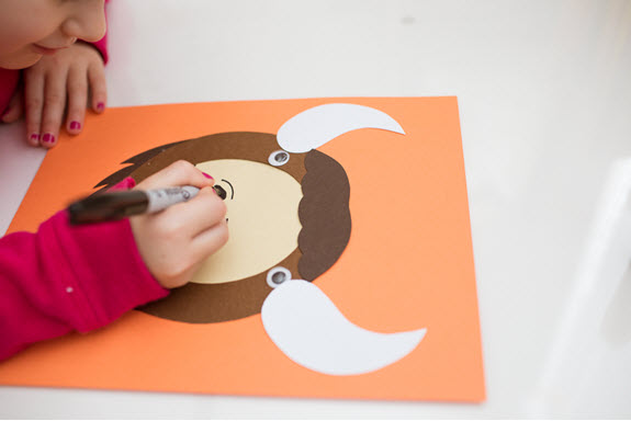 child draws a nose on her uppercase letter O craft