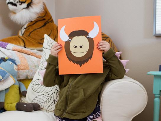 child hides behind her uppercase letter O craft