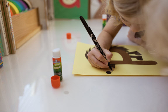 child draws a mouth on her uppercase letter P craft