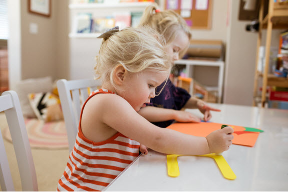 child glues her lowercase u craft