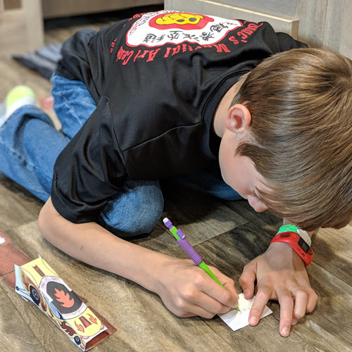 boy writes spelling word on the back of drag race track card