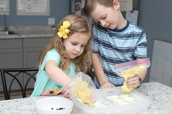 Children filling in deviled eggs